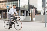 A man rides a bicycle in a city