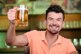 Man raising a glass of beer in cheer