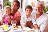 Grandparents eating at a restaurant with their grandchildren