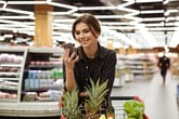 A woman uses her smartphone at the grocery store