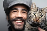 Man's smiling face with grey tabby cat face.