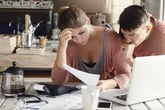 Distressed looking couple studying bills