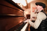 A bearded senior in a hat sings and plays piano music
