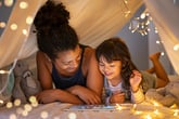 Mother and daughter playing on a tablet in a tent