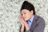 Young woman sleeping on money