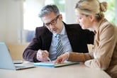 A financial adviser coaches a woman on investing