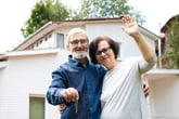 Retired couple in front of their home