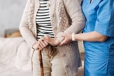 A nurse helps an older patient walk with a cane