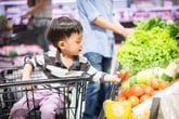 Child in a grocery story produce department