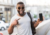 A Black man in sunglasses and a t-shirt excitedly points at his new cell phone