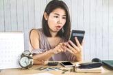 Shocked woman using a calculator