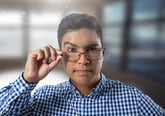 A skeptical worker raises an eyebrow while lowering his glasses