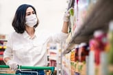 Woman shopping for groceries in a mask and gloves