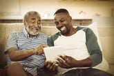 Happy senior using a tablet with his son