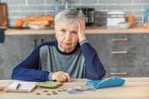 Unhappy senior woman counts money