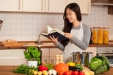 Woman reading a cookbook in her kitchen