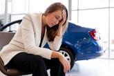 Upset woman sitting in car dealership