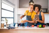 Happy couple using a tablet while cooking