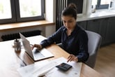 Woman on laptop with calculator paying bills