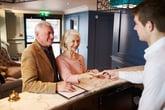 senior couple checking into hotel
