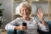 Senior woman waves goodbye to her phone