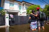 Couple outside their flooded house