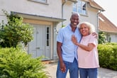 Happy senior couple in front of their house