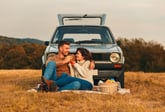 Couple having a picnic in front of an old car