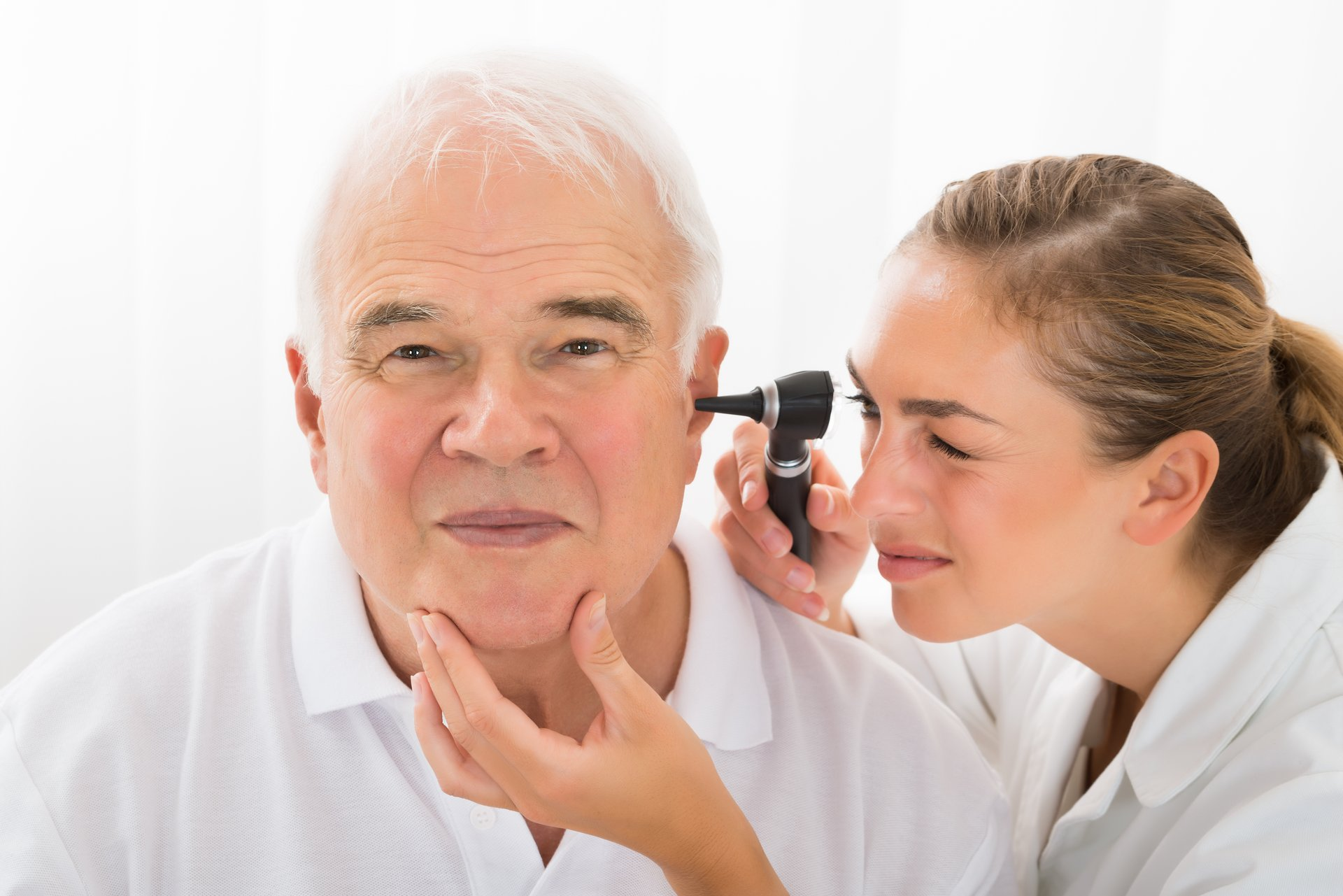 Doctor using scope to look inside man's ear.