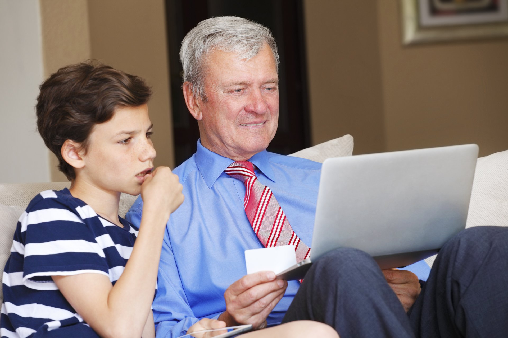 Man teaching his grandchild how to use a credit card