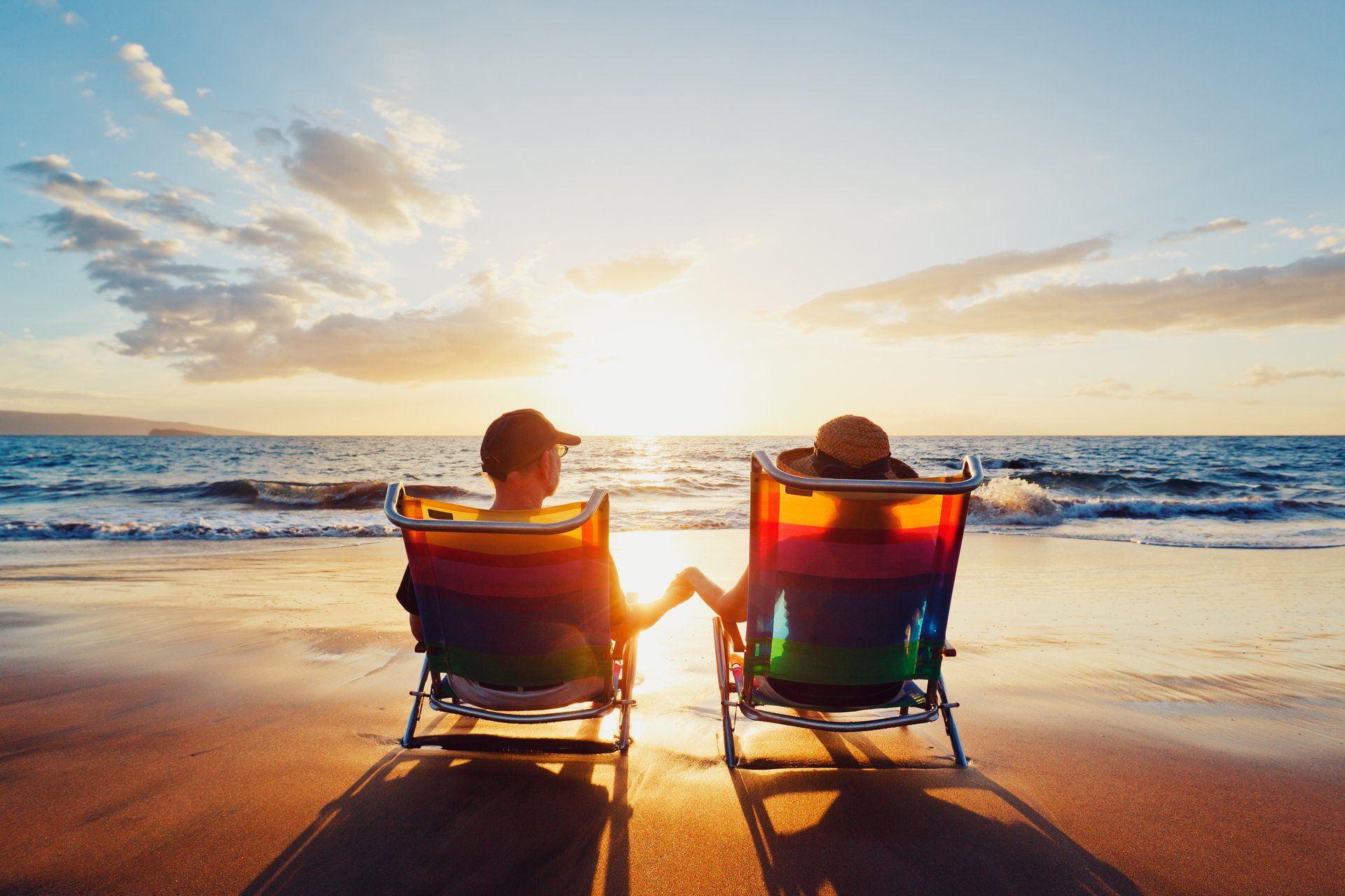 A couple watches the sunset at the beach