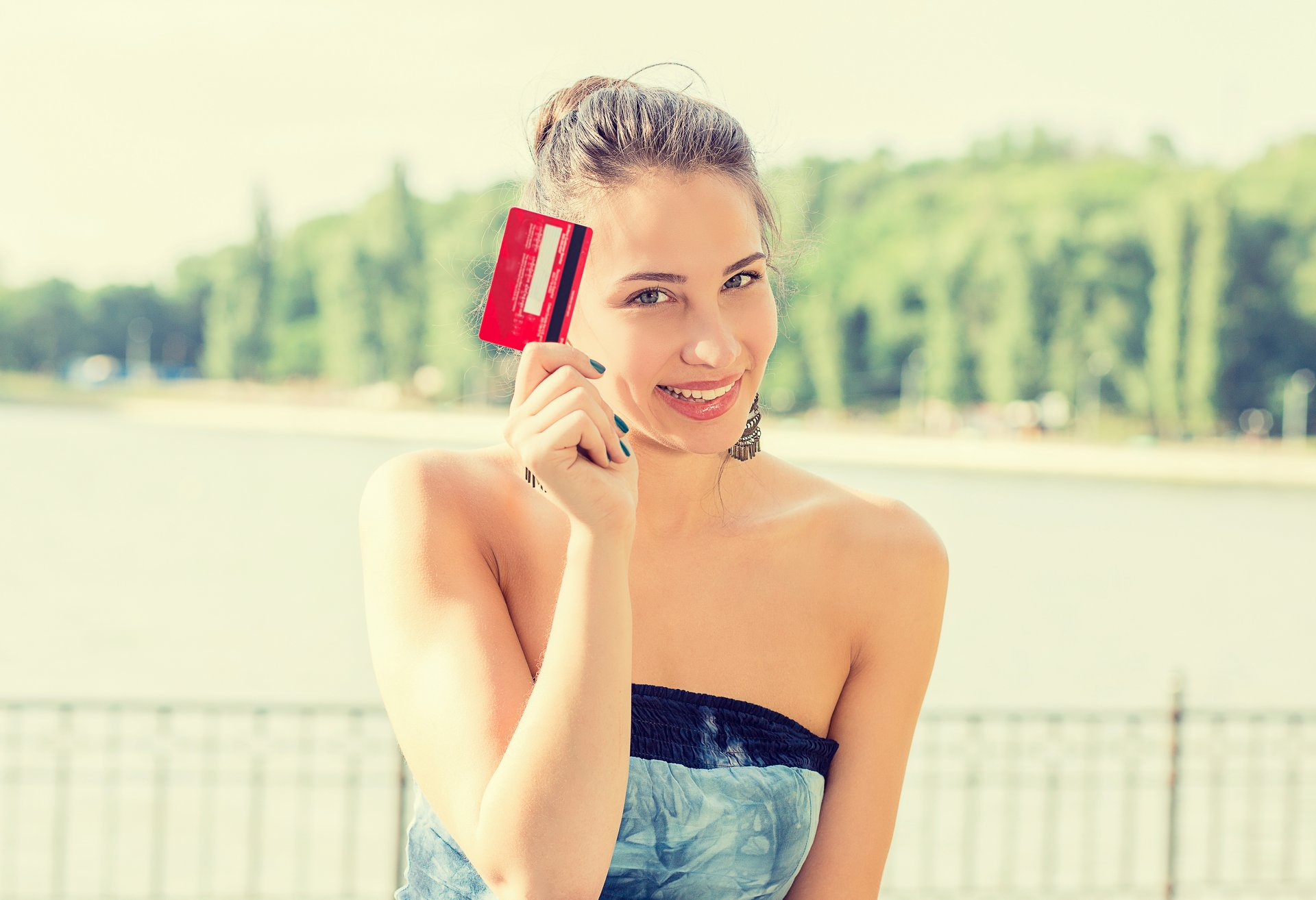 A woman holds up her credit card
