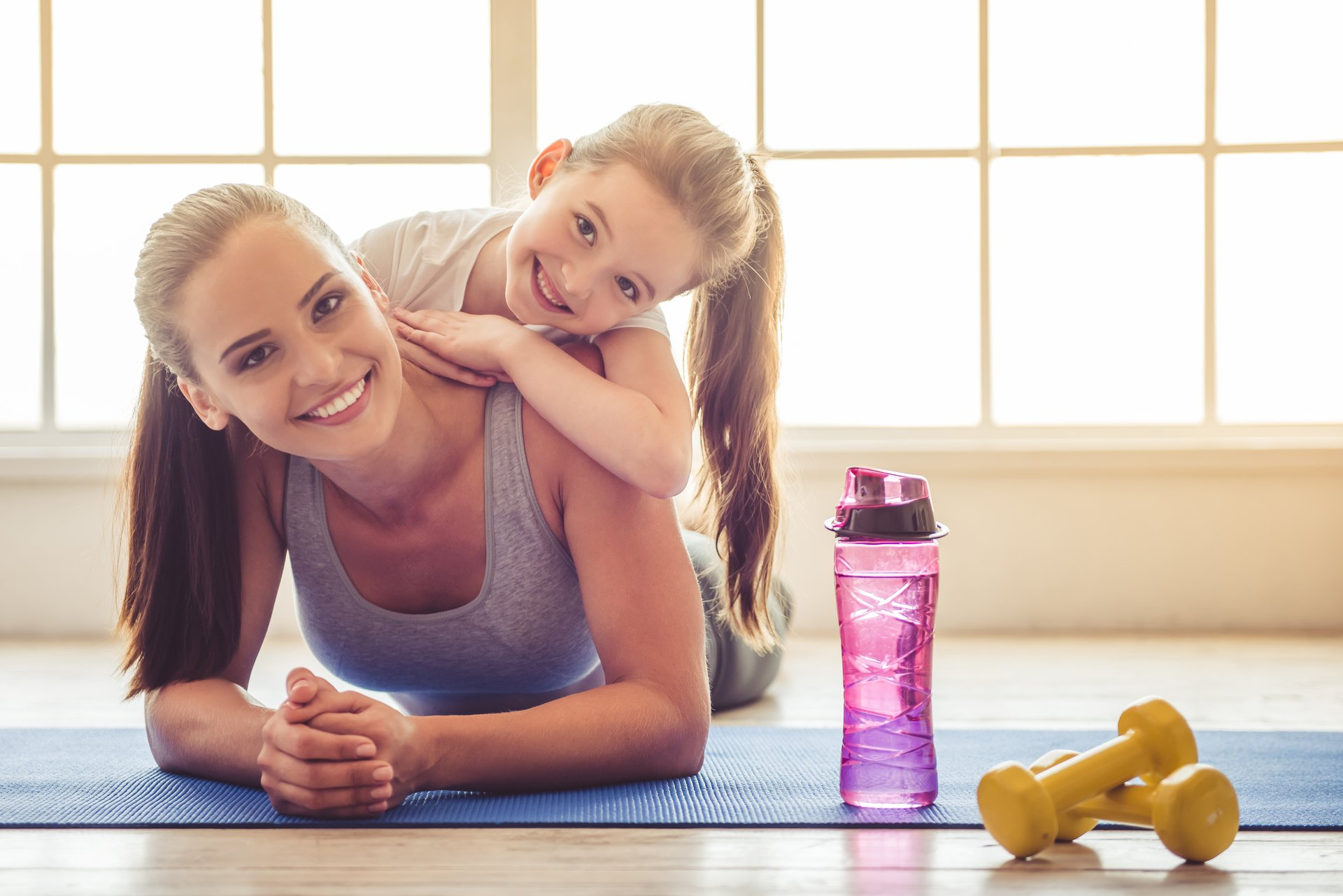 Mother and young daughter at gym