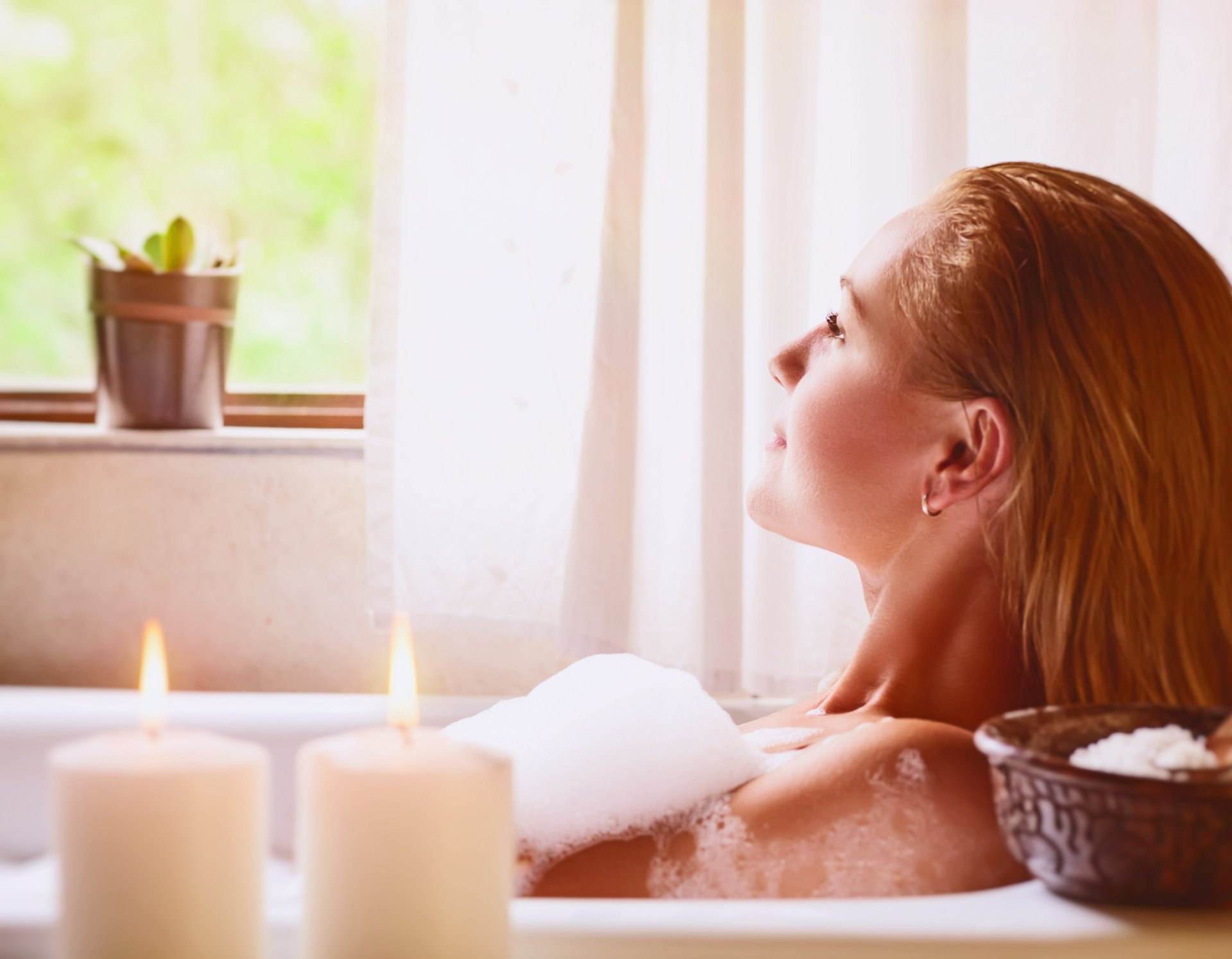 A young woman relaxes in the bath tub with candles
