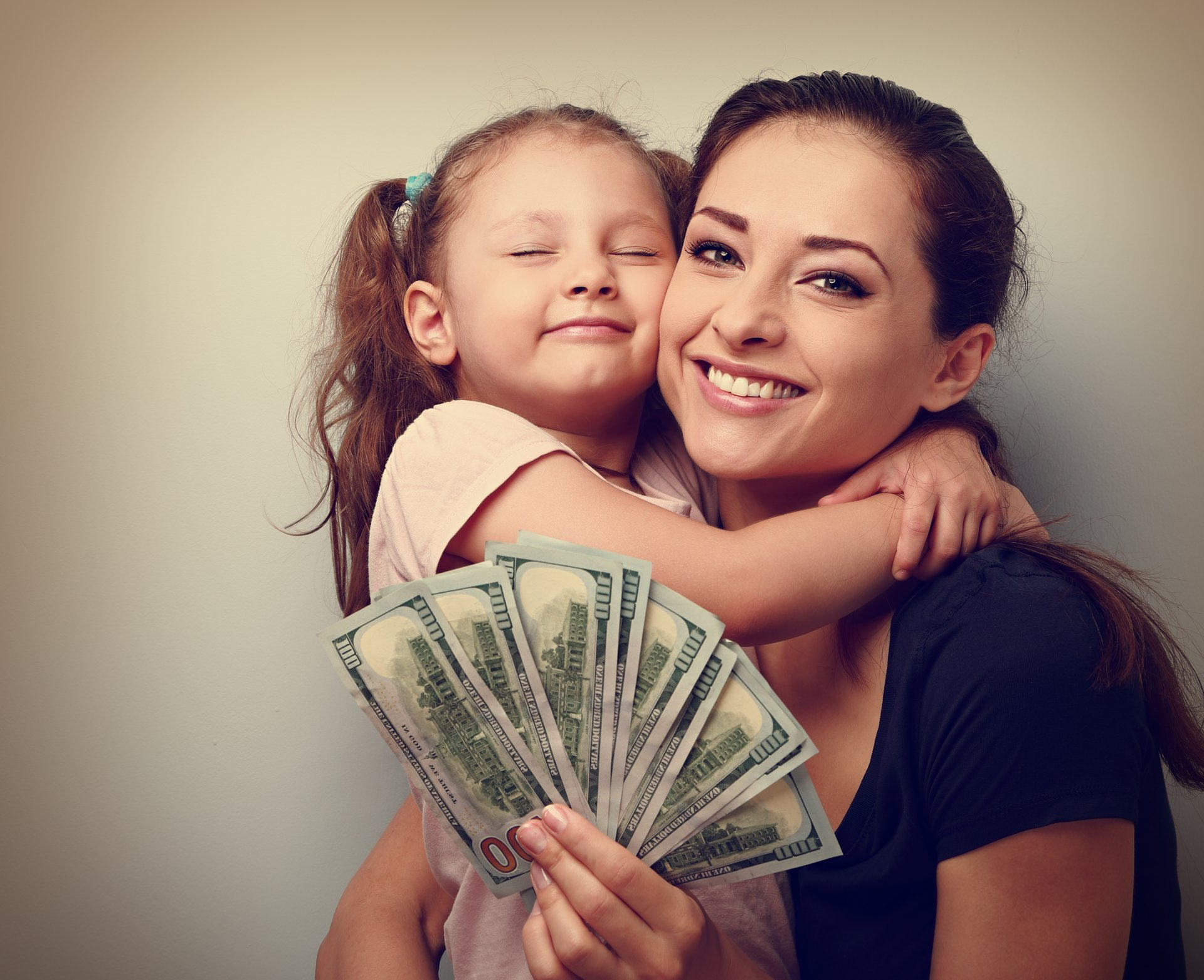 Smiling mother and happy daughter with dollars.