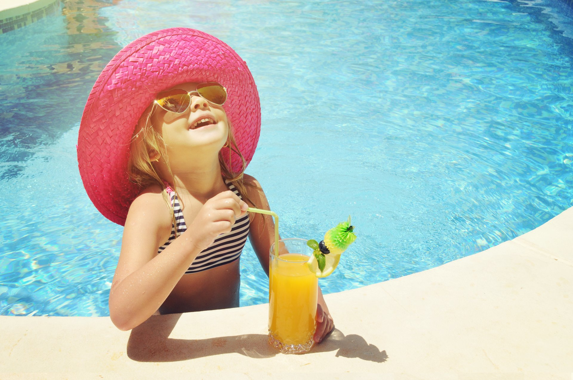Girl with drink in pool
