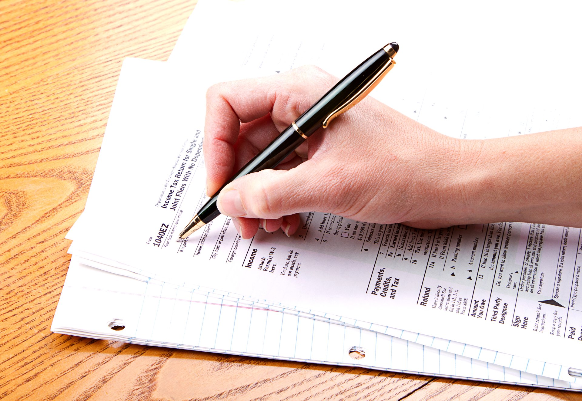 Person filling out IRS Form 1040EZ for federal income taxes