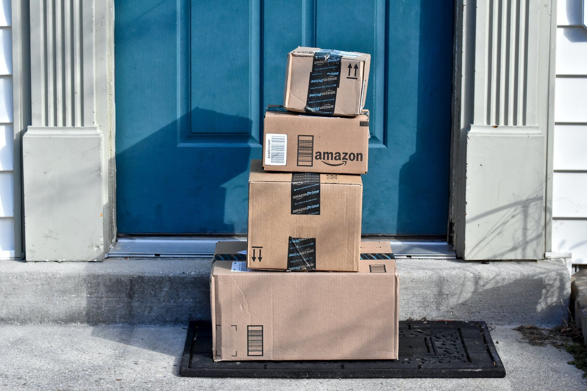 Packages from Amazon are piled in front of a door