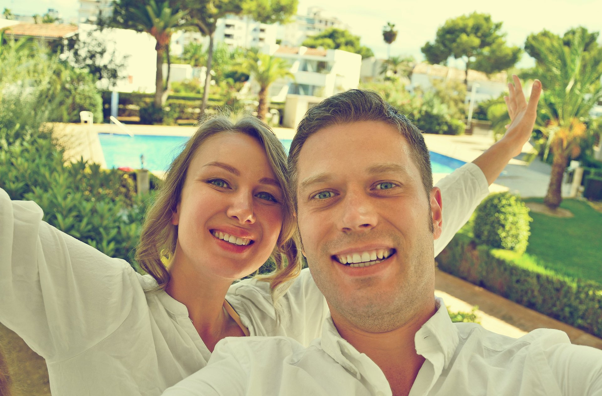 A couple takes a selfie from their hotel room balcony