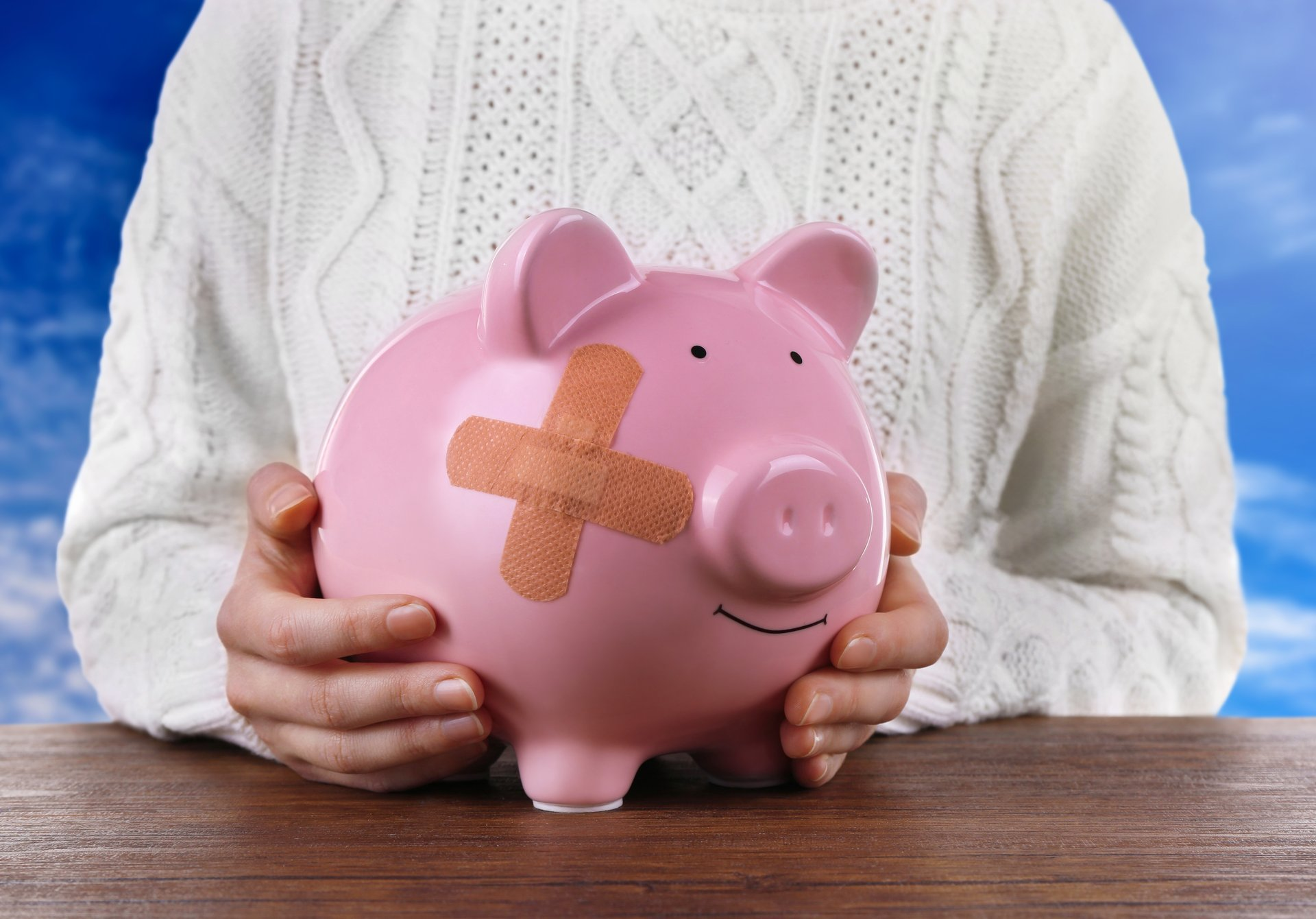 A woman holds a bandaged piggy bank