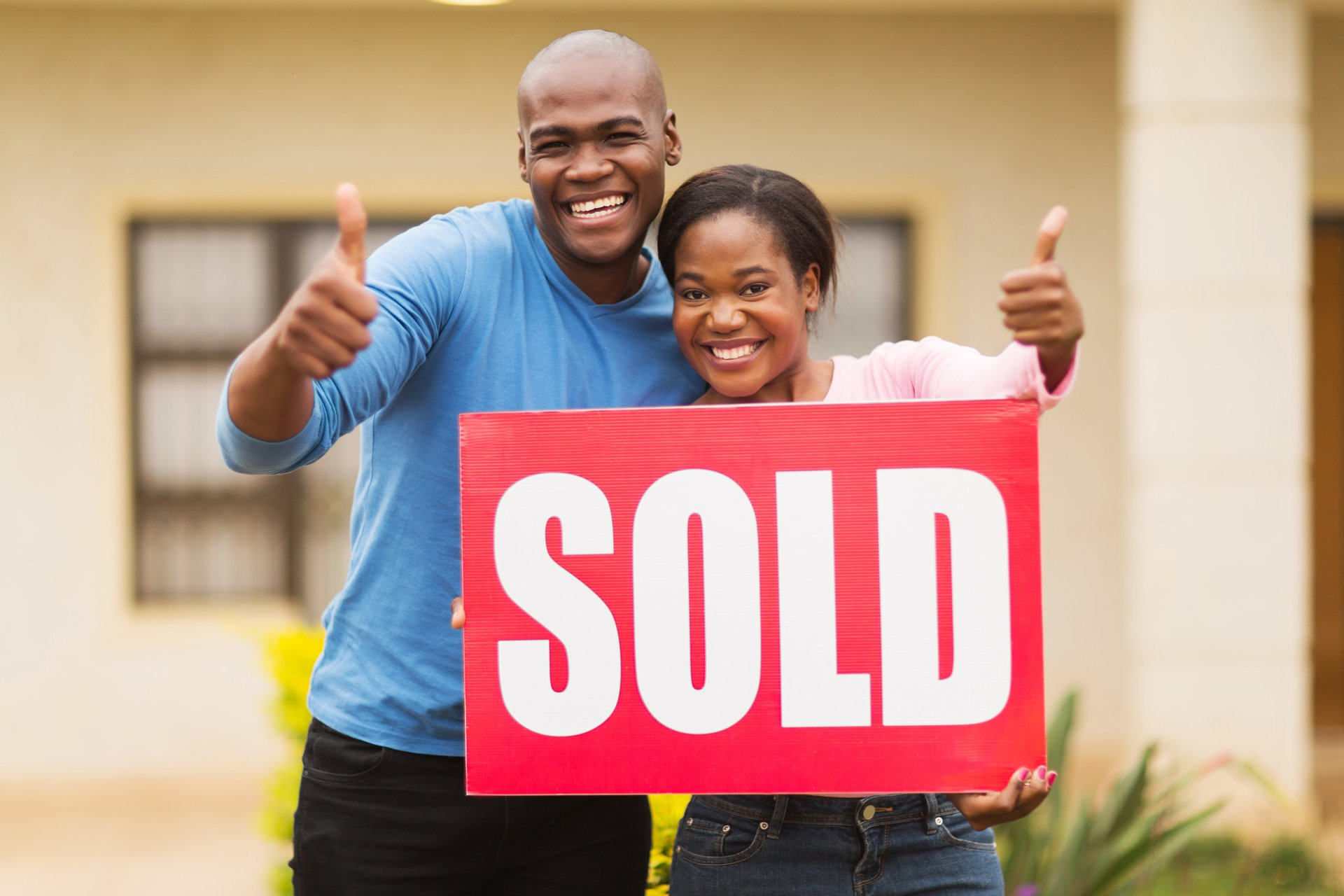 "A couple holds a ""Sold"" sign in front of their home"