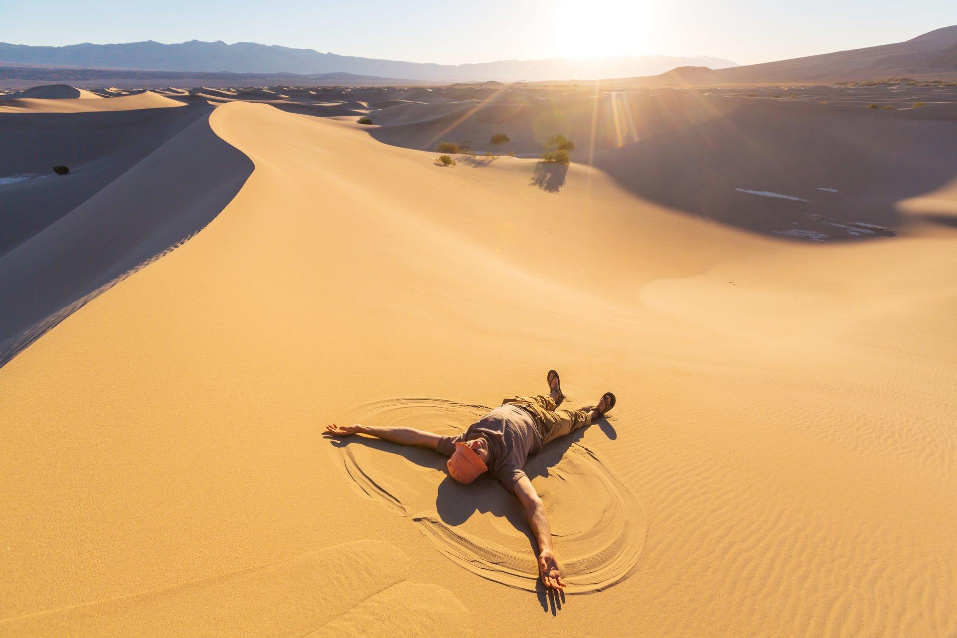 Man lying on sand dune