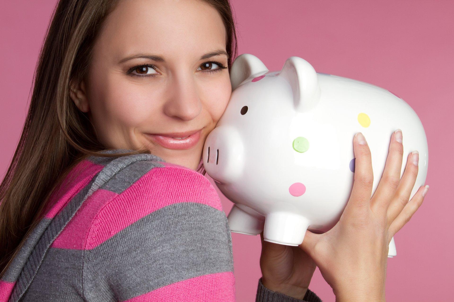 A woman hugs a piggy bank