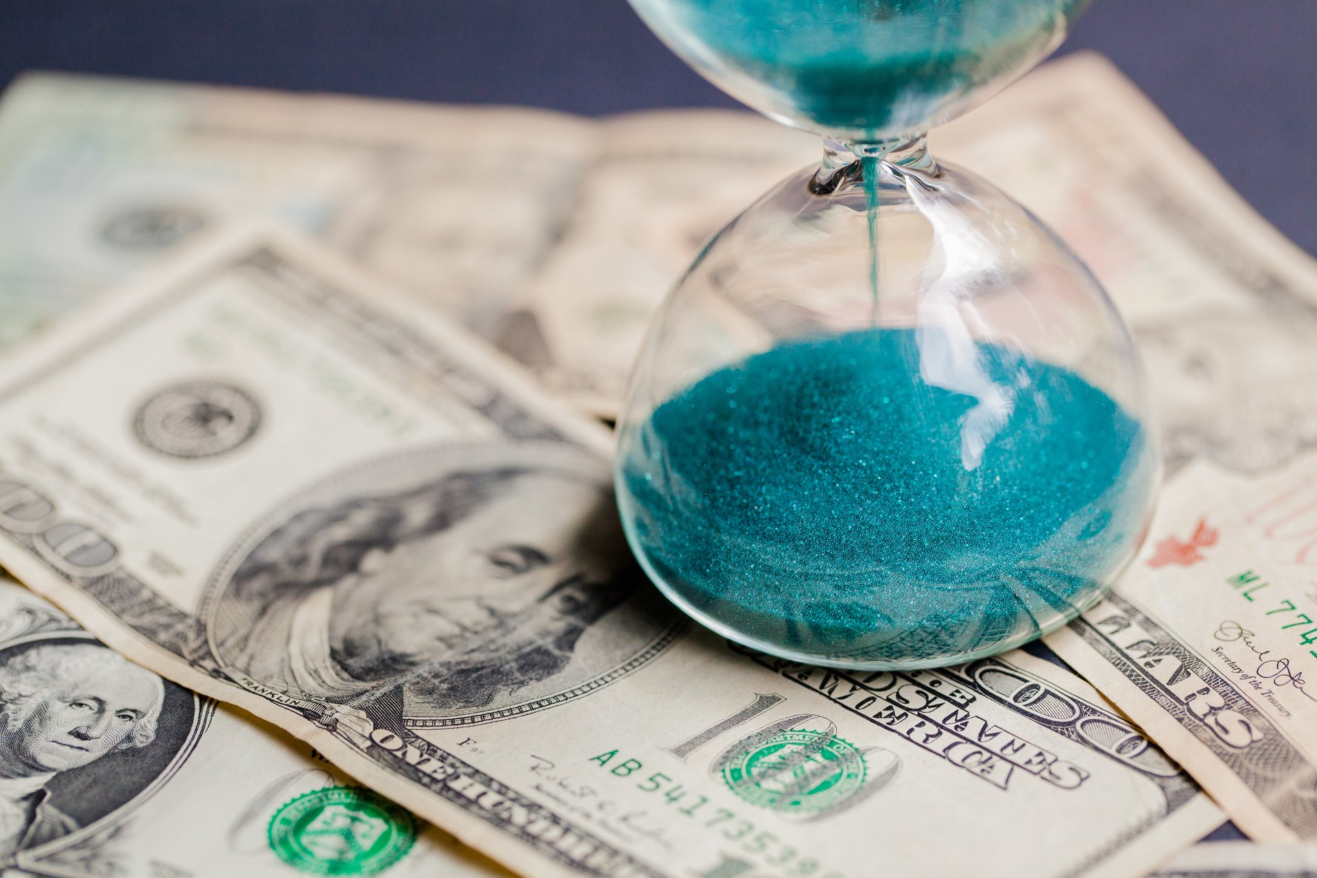 Sand flows through an hourglass next to money