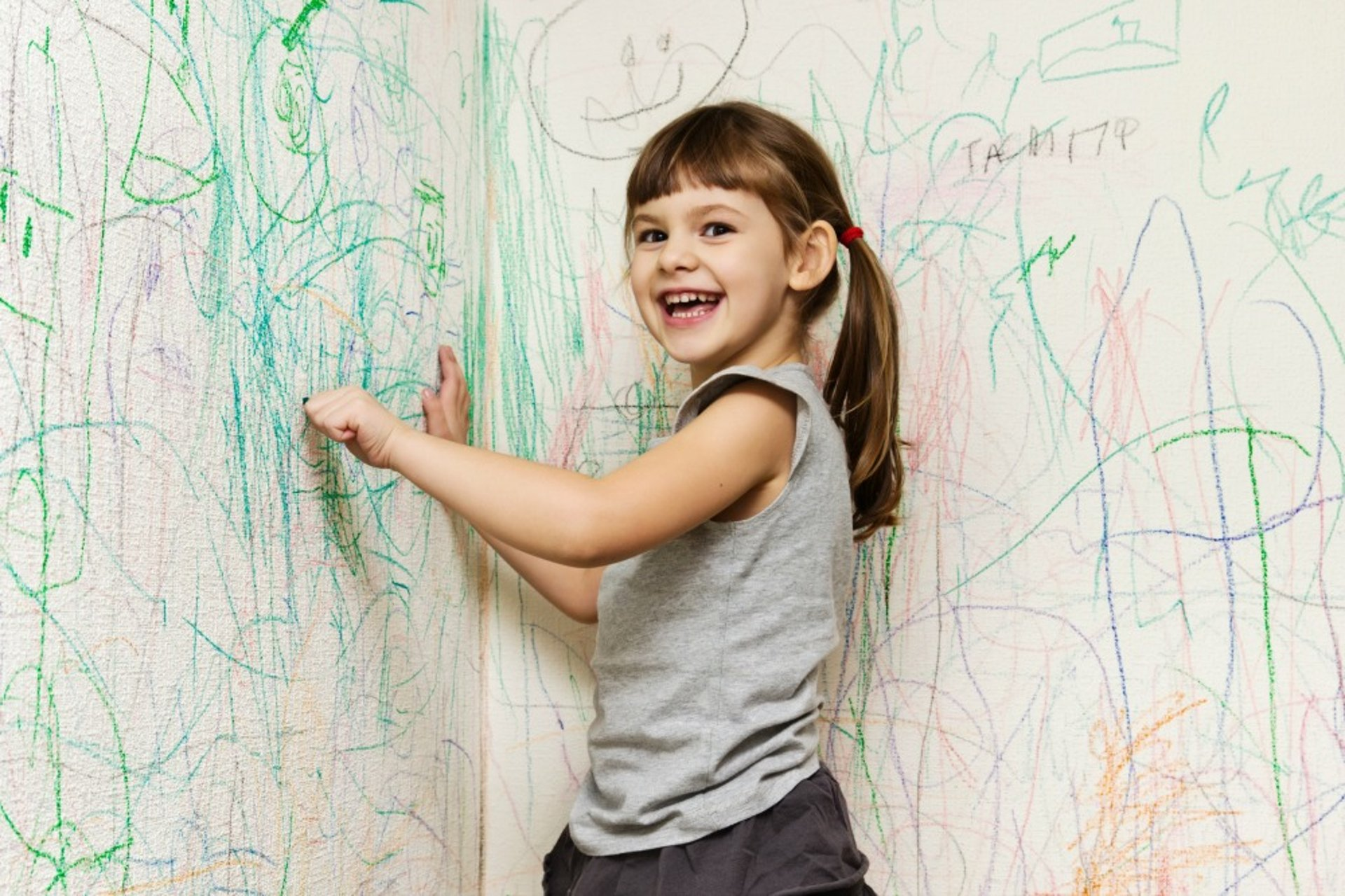 Girl drawing on wall with crayon