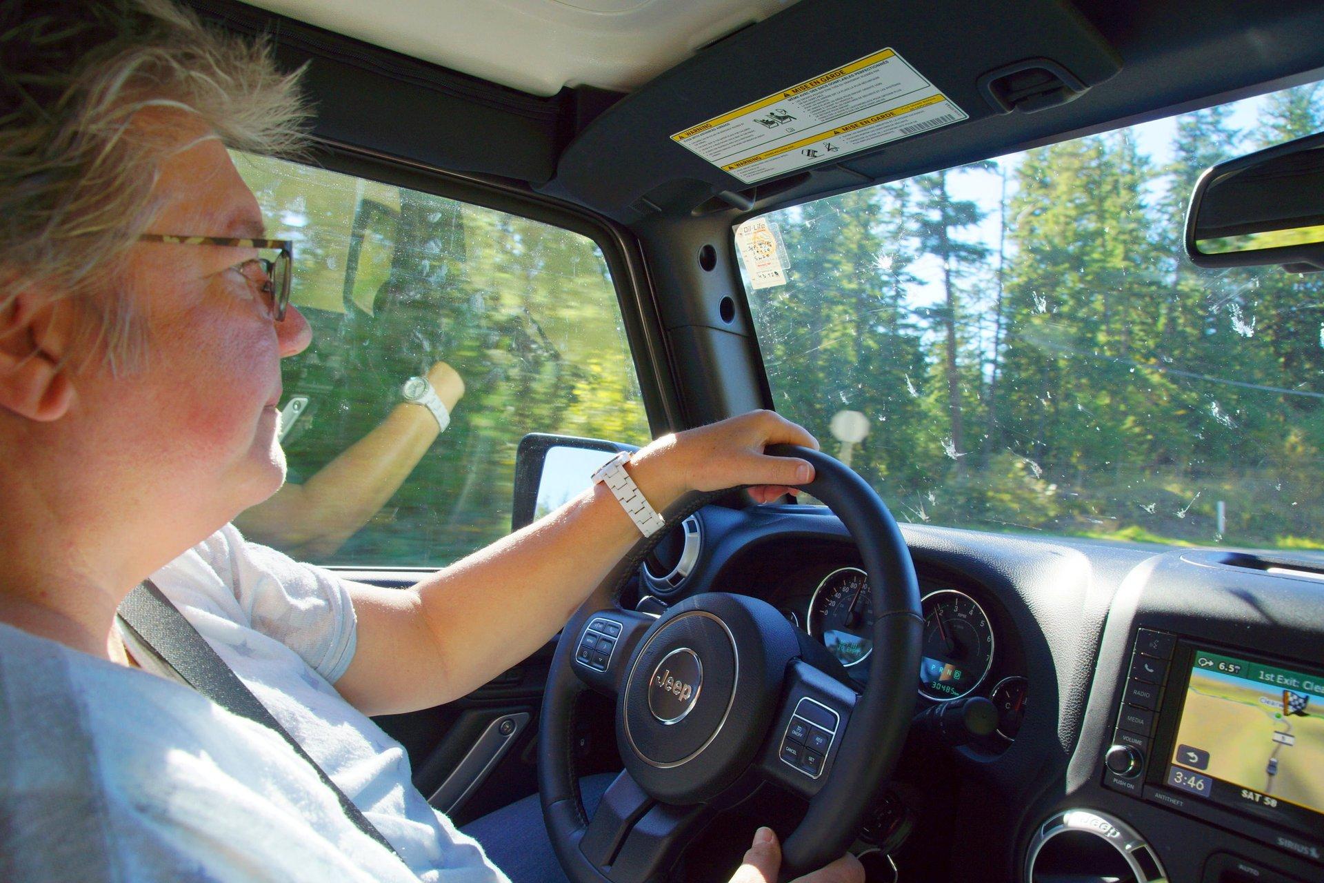 A woman drives a Jeep Wrangler