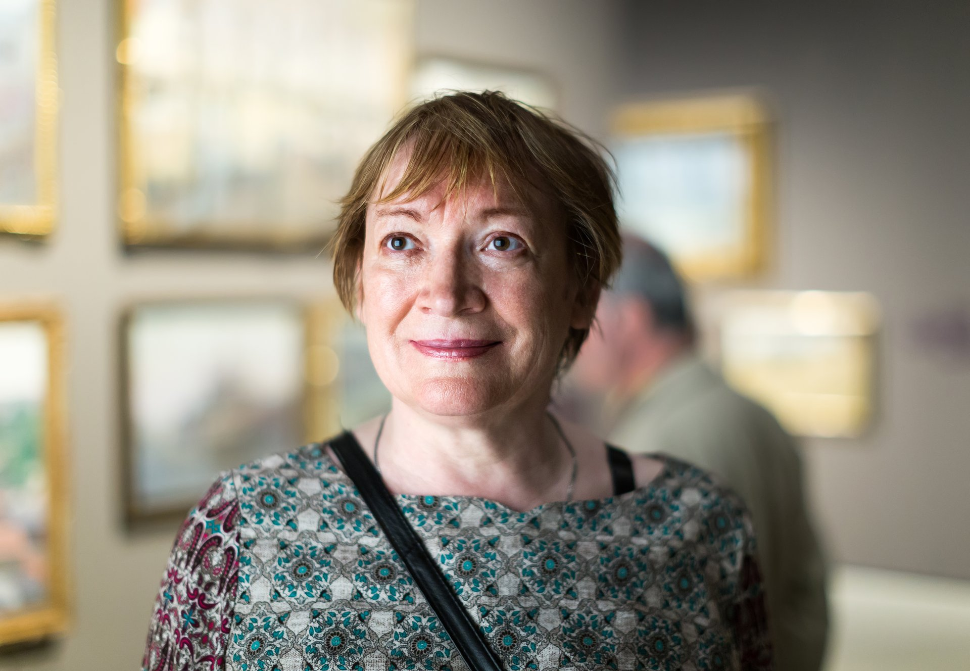 A senior woman looks at paintings in an art museum