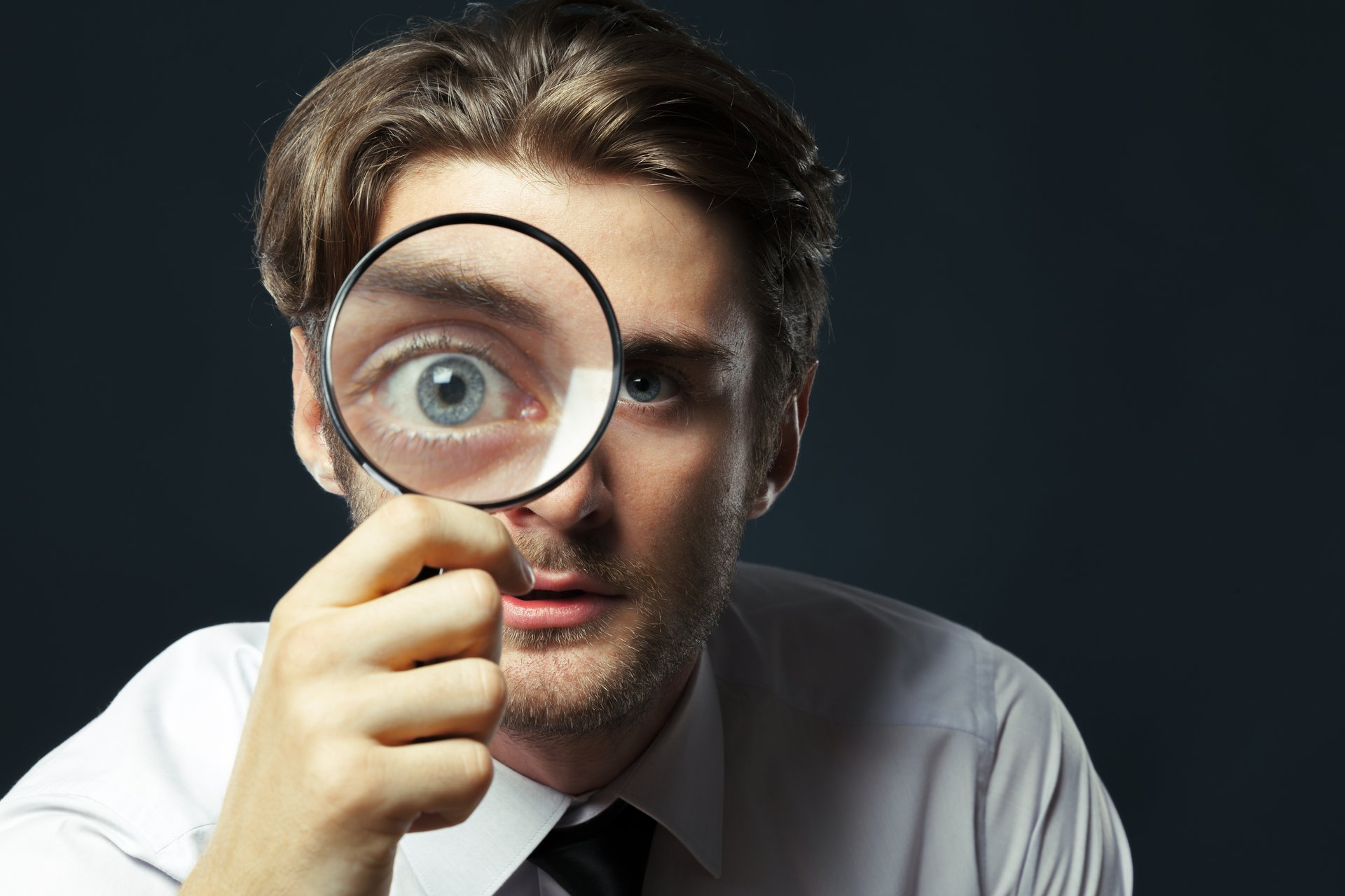 A man holds up and looks through a magnifying glass