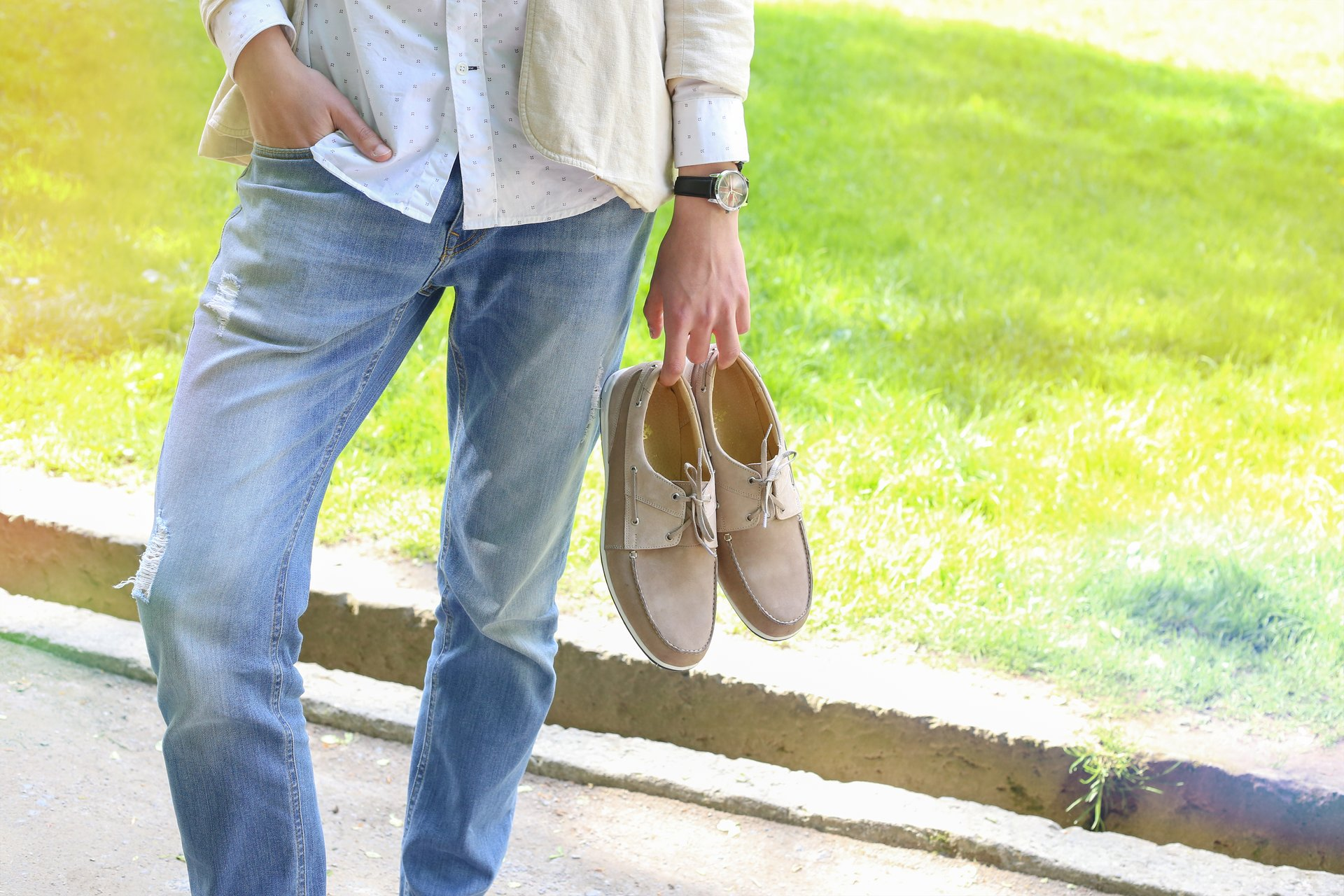 Student walking barefoot in the park holding trendy shoes in hands.