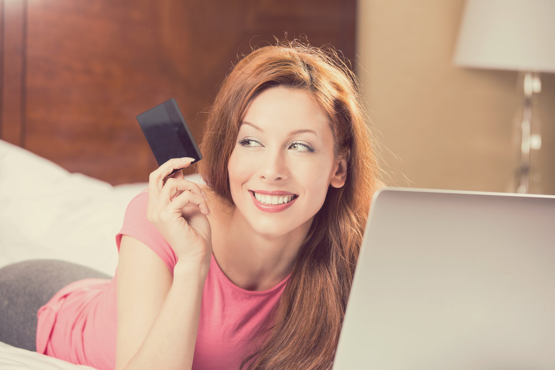 Woman holding credit card, looking at computer